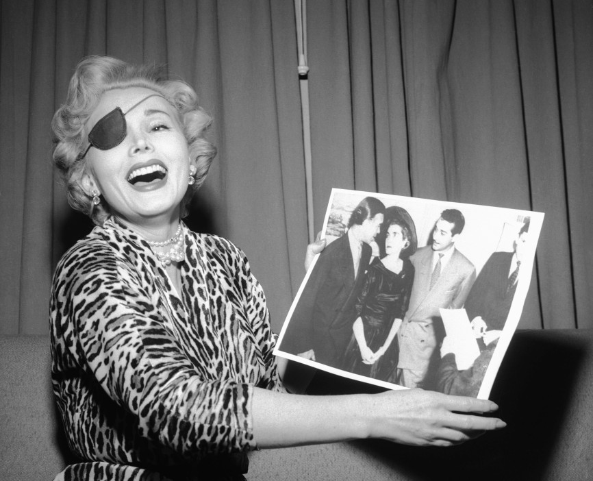 """03 Jan 1954, Las Vegas, Nevada, USA --- 1/3/1954-Las Vegas, NV: """"Look how unhappy they both look!"""" Zsa Zsa Gabor laughs as she is handed a United Press Telephoto of the Porfirio Rubirosa and Barbara Hutton wedding shortly after the ceremony on Dec.30 in New York. In her suite in the Hotel Last Frontier the Hungarian beauty sniffed that she was """"very, very happy"""" that Rubirosa got married because now he can pay her the $5,600 hotel bill he owes her. Zsa Zsa has already explained that she's wearing a patch to cover a black eye she says Rubirosa gave her. --- Image by © Bettmann/CORBIS"""